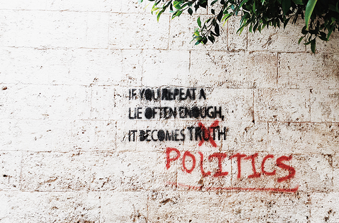 White brick wall with black writing: If you repeat a lie often enough, it becomes truth. The word 'truth' has been crossed out with red paint and replaced with the word 'politics'.