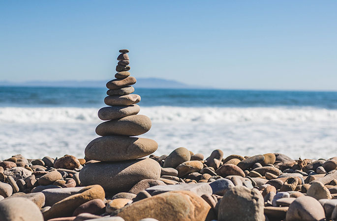 Rocks balancing on each other with a beach in the background.