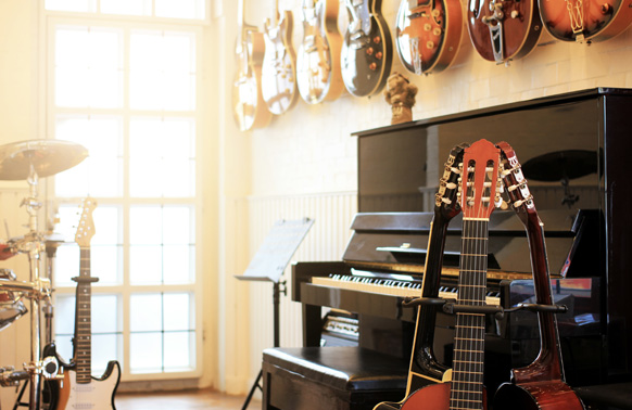 A music room with several guitars hanging on the wall. A drum kit and a piano are in the midground. Three guitars in stands are arranged together close to the piano in the forground.