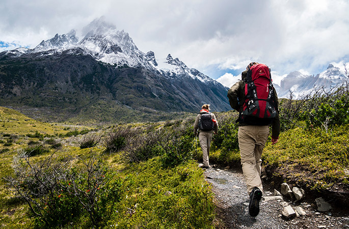 Two people hiking along a dirt path with snow-capped mountains in the background.