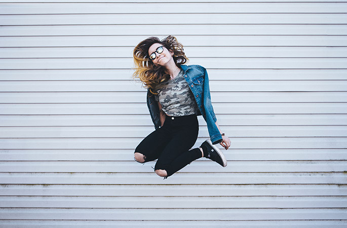 Woman with denim jacket and reflective glasses jumping in the air.